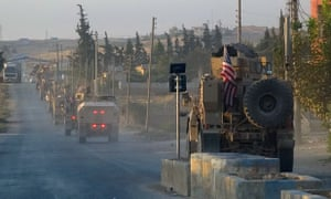 US military vehicles travel down a main road in northeast Syria