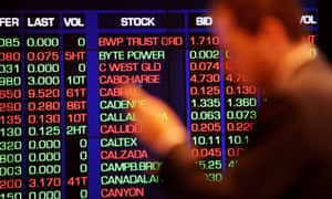 A city office worker watches the share market prices at the Australian Stock Exchange