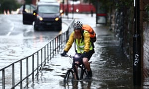 Man cycling along pavement through water up to his hubs