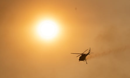 A helicopter is seen over the Orroral Valley as fire spread through the Namadgi national park in January in Canberra, Australia.