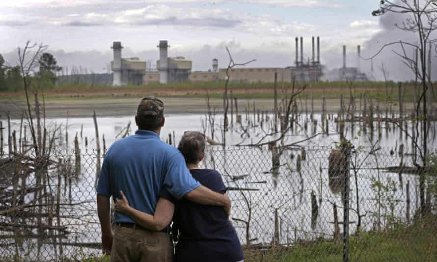 In this 25 April 2014, file photo, Bryant Gobble and his wife, Sherry, look from their yard across an ash pond full of dead trees toward Duke Energy's Buck Steam Station in Dukeville, North Carolina.