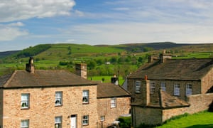 Stone cottages in the elevated village of Reeth, with the Yorkshire Dales in the background.