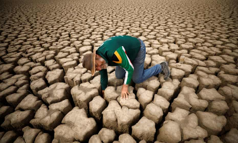 A hydrologist checks cracks in the dried up municipal dam in the drought-stricken town of Graaff-Reinet, South Africa, in November 2019.