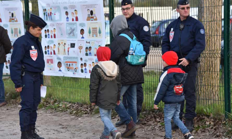 Children are escorted from the Calais migrant camp following its demolition last month