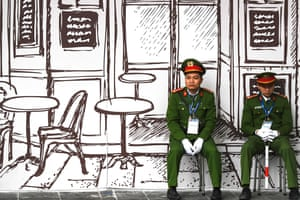 Police officers sit on stools in Hanoi