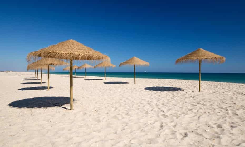 Straw umbrellas on empty white sand beach with clear sea behind, Ilha do Farol, Culatra barrier island, Olhao
