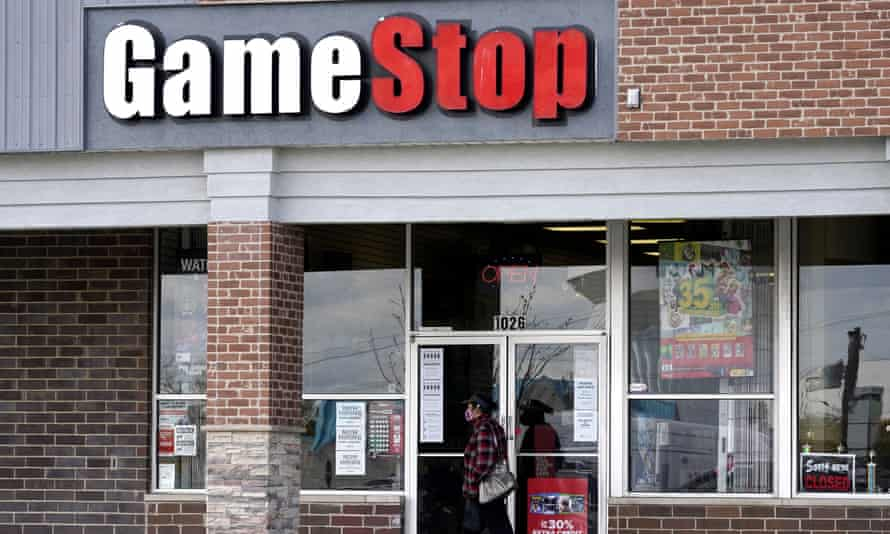 A woman wears a face mask as she walks past a GameStop store in Des Plaines, Illinois, US.