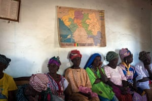 Women of Fermessadou, sitting below Guinea map