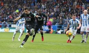 Luka Milivojevic sends Huddersfield goalkeeper Jonas Lössl the wrong way from the penalty spot.