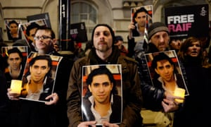 Protesters take part in an Amnesty International protest in front of the Saudi embassy in London against the flogging of Raif Badawi.