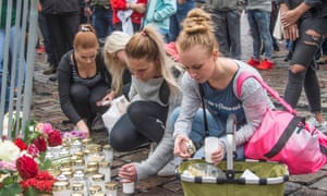Women place candles and flowers at the scene of the attack in Turku on Friday.