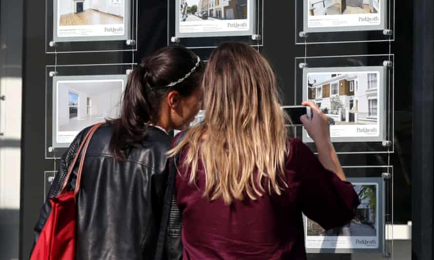 two young women looking at houses for sale in an estate agent's window.