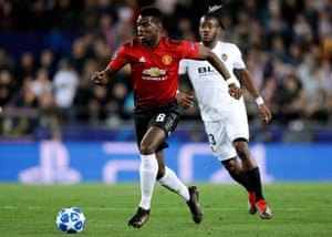 Paul Pogba of Manchester United surges forward as Valencia's Michy Batshuayi looks on.