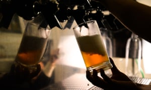 Beer being poured into glass in a pub.