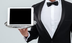 A butler in tuxedo with bowtie holding blank screen tablet on tray.