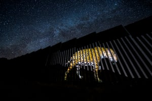 The image of a jaguar is projected on to a section of the US-Mexican border wall