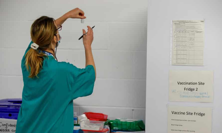 A medical woerk holds a vial of a COVID-19 vaccine as she works at a temporary vaccination centre set up in Derby