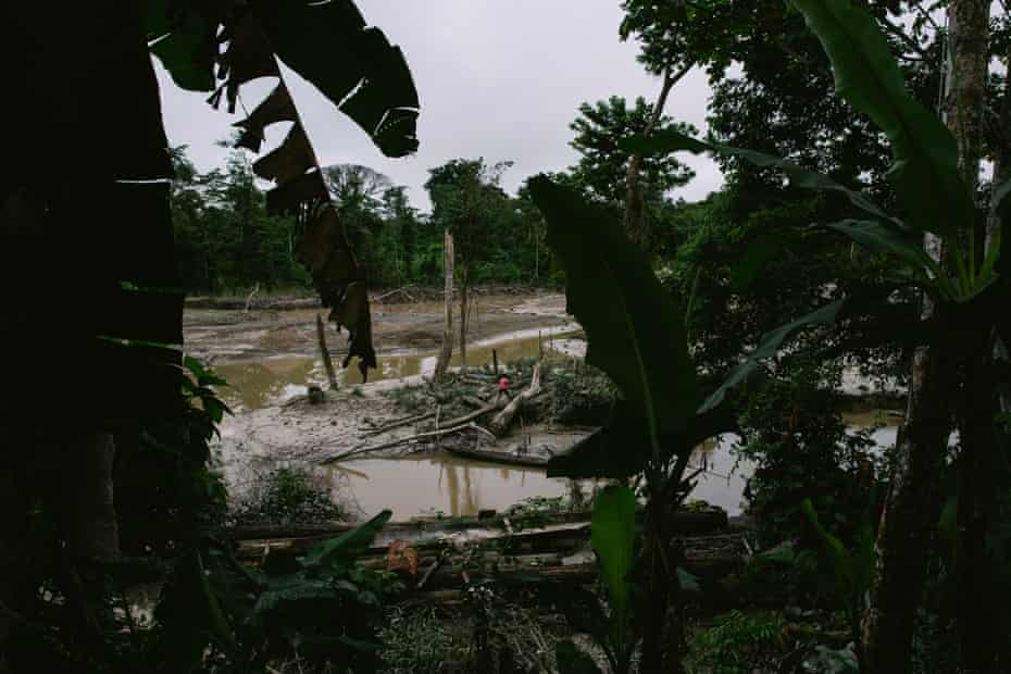A woman walks in the destroyed land along the waterway of the Quebrada Pastacillo