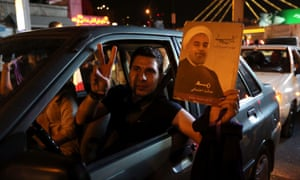 An Iranian man holds up a portrait of Hassan Rouhani
