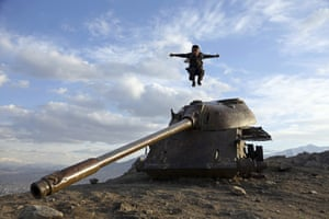 Kabul, Afghanistan. A boy jumps off the turret of a Soviet tank on a hilltop on the the outskirts of the city