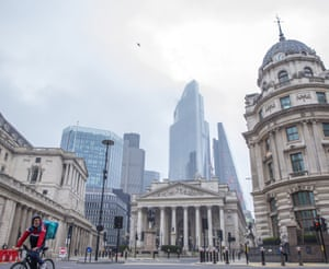 A cyclist with a backpack for food delivery service runs through a quiet City of London during England's third lockdown on the day the chancellor sets out tax and spending plans in the budget to help repair the UK economy.