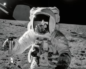 apollo 12 lunar module pilot alan bean on the surface of the moon holding a special environment sample container