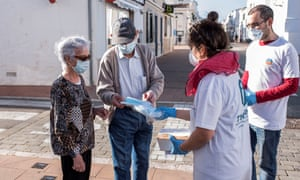 Workers inform people about the new measures and timetables following the easing of lockdown in Menorca, Spain.
