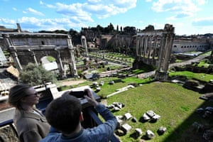 Tourists take pictures of the closed Ancient Forum from the outside in Rome