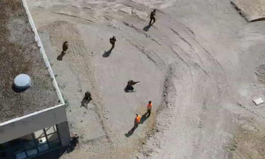 Still from drone footage shows men in military-style gear moving in formation while holding weapons at a former barracks in Mosbach