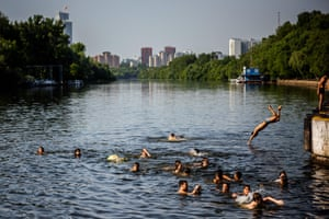 Youths dive into the Moskva River to cool off