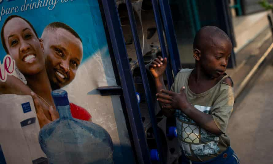A street child stands next to a water bottle holder outside a shop in Bujumbura