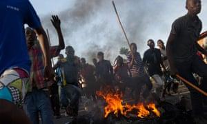 Protesters run across a fire towards police lines in the Musaga neighbourhood of Bujumbura, on Monday.