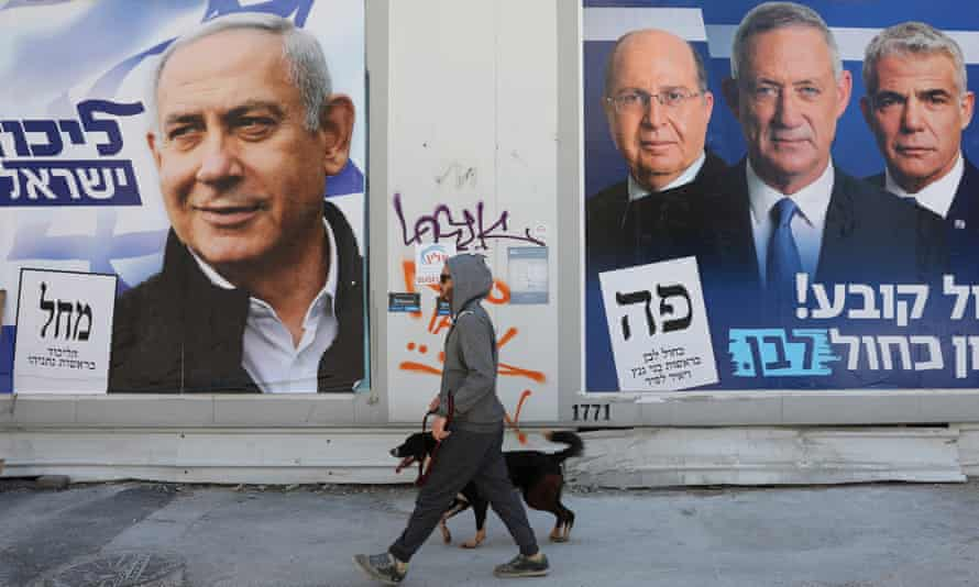 A man walks his dog between election campaign billboards for Benjamin Netanyahu (L) and Benny Gantz in Tel Aviv.