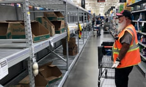 A shopper looks at a cleaned-out toilet paper aisle in a Phoenix, Arizona Walmart Supercenter Friday, March 20, 2020.