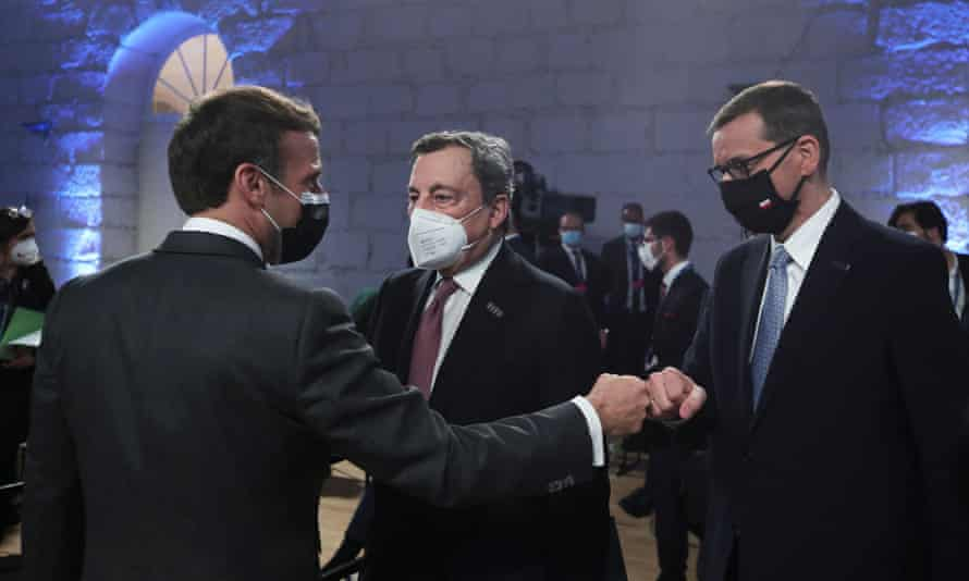 French president, Emmanuel Macron, fist bumps Poland's prime minister, Mateusz Morawiecki, and Italy's Mario Draghi during the opening ceremony of an EU summit in Porto, Portugal.