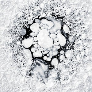 Frozen in ice methane bubbles in the Arctic tundra of Alaska by photographer Kajita Ryota.