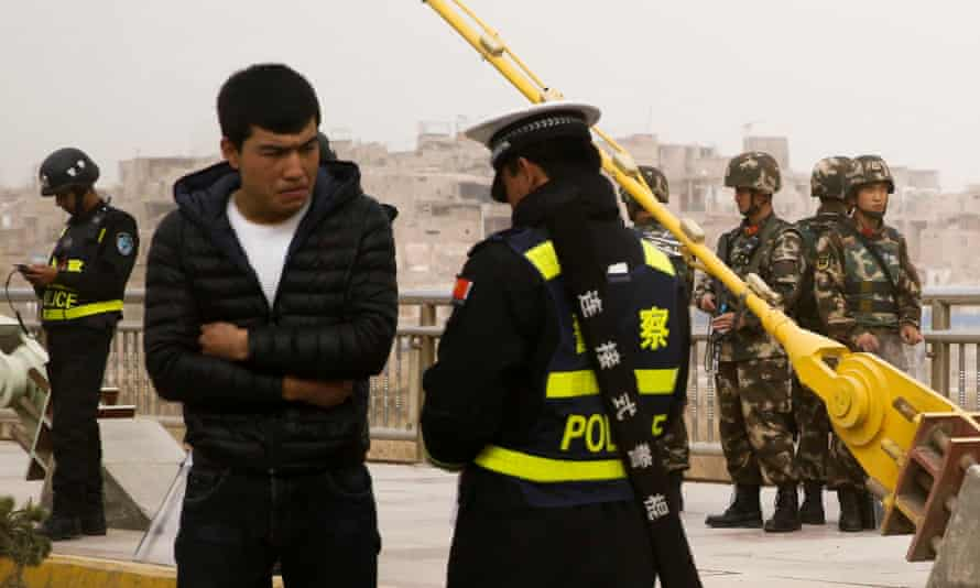 A police officer checks the identity card of a man as security forces keep watch in a street in Kashgar, Xinjiang