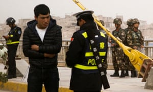 A police officer checks the identity card of a man as security forces keep watch in a street in Kashgar.