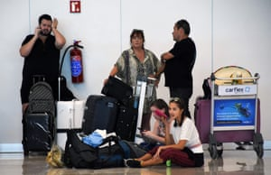 Stranded passengers waiting near the closed Thomas Cook check-in desk at the International Airport in Cancun, Mexico, today.
