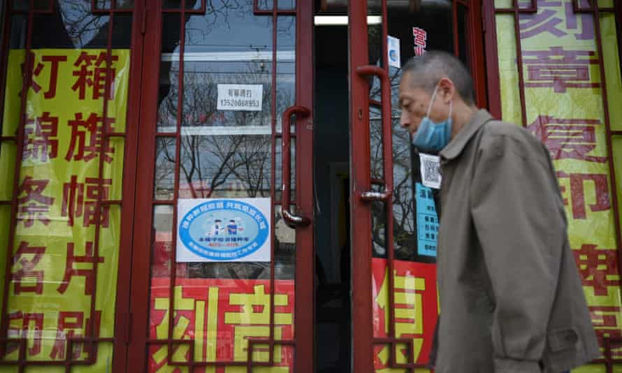 A man walks past a blue sign indicating workers' Covid vaccination rates on the door of a printing business in Beijing.