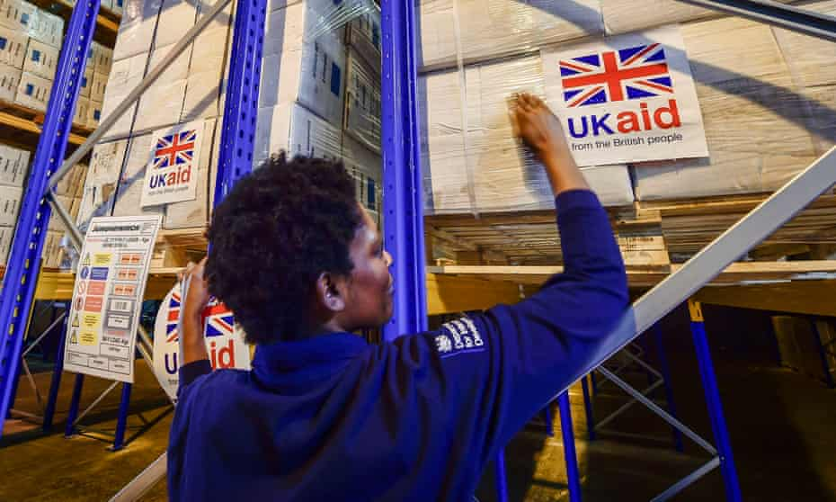 Logistics officer Beverley Sarpong placing UK Aid stickers onto cargo pallets containing British aid items destined for areas suffering humanitarian crisis at Cotswold Airport, Kemble