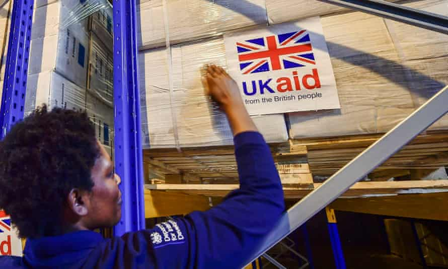 Logistics officer Beverley Sarpong placing UK Aid stickers onto cargo pallets containing British aid items destined for areas suffering humanitarian crisis at DFID's UK Disaster Response Operations Centre at Cotswold Airport, Kemble.