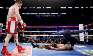 Canelo Alvarez, left, watches after knocking down Amir Khan during their WBC middleweight title fight