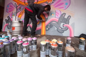 A graffiti artist sprays the finishing touches on his piece