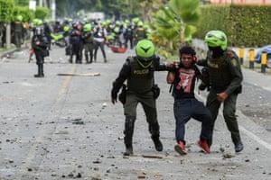 Colombian police officers arrest a demonstrator