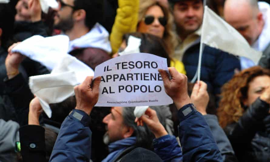 """A demonstrator holds a placard reading """"The treasure belongs to the people"""", during a protest against the Church gaining any control over the treasure of Saint Gennaro."""