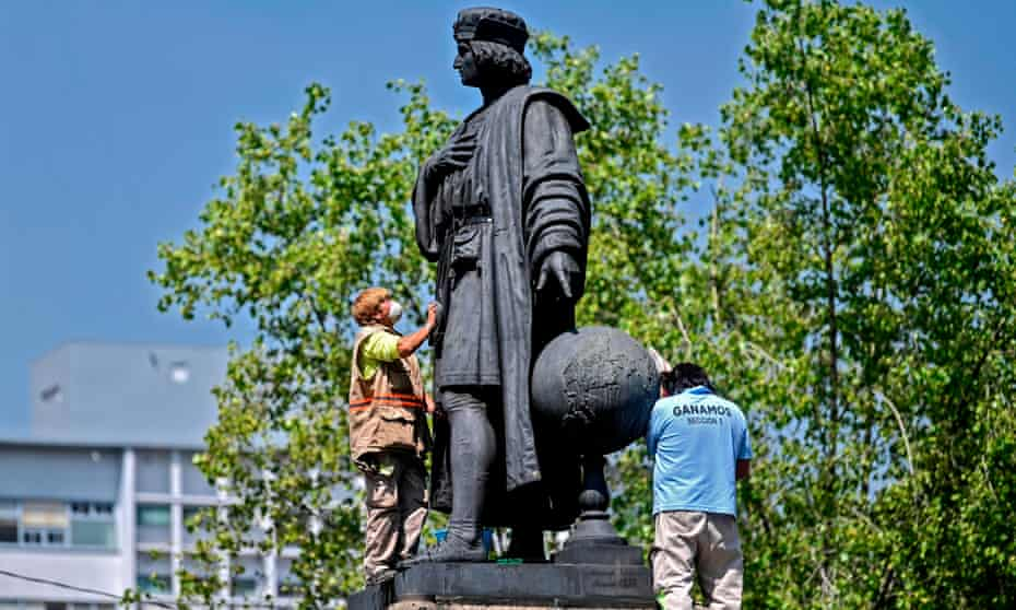 Municipal workers clean a statue of Christopher Columbus on Mexico City's Reforma boulevard.
