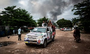 Campaign messages blare from a car as smoke rises from a fire at the electoral commission in Kinshasa on 13 December.