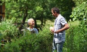 Two men chatting over plants in garden