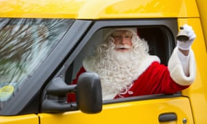 Santa Claus in a yellow van ringing a bell.
